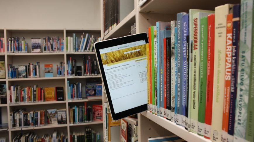 Tabletti kirjojen välissä kirjahyllyssä.