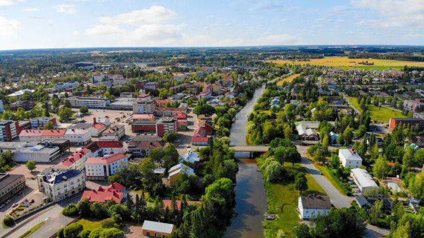Maaseutukaupunki kuvan keskellä joki ja taustalla peltoja