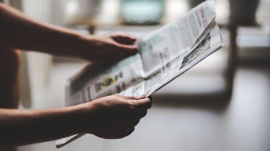 Ihminen lukee sanomalehteä.